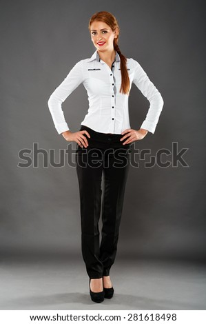 Full length of a confident attractive businesswoman on gray background - stock photo