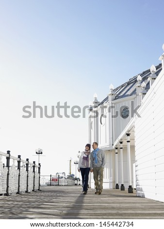 Full length of a couple holding hands and walking along pier - stock photo