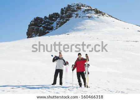 Full length of a couple with ski boards standing on snow covered landscape against clear blue sky