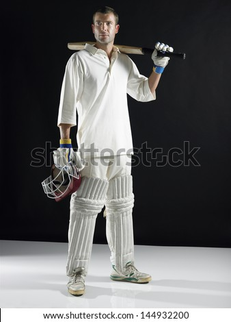 Full length of a cricket player holding bat on shoulder against black background - stock photo