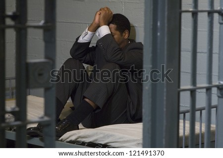Full length of a depressed businessman sitting in jail - stock photo