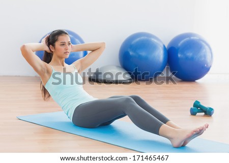 Full length of a determined young woman doing sit ups in fitness studio