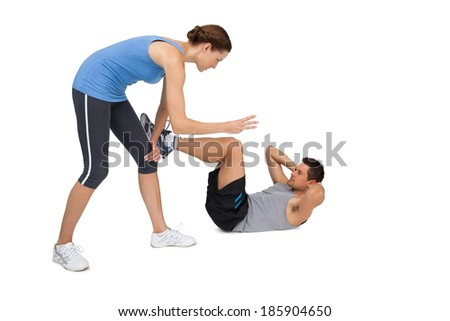 Full length of a female trainer assisting man with crunches over white background