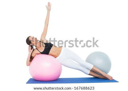 Full length of a fit young woman stretching on fitness ball over white background