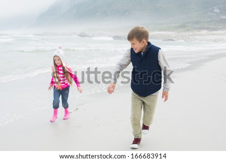 Full length of a happy brother and sister running at the beach - stock photo