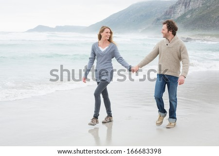 Full length of a happy casual young couple holding hands and walking at the beach - stock photo