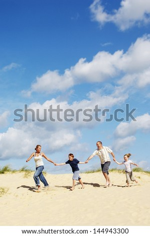 Full length of a happy family holding hands and running down sand dune on beach - stock photo