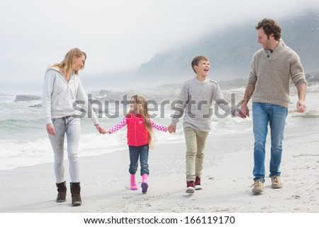 Full length of a happy family of four walking hand in hand at the beach - stock photo