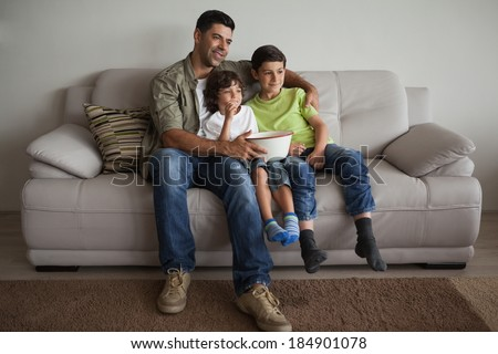 Full length of a happy father and sons with popcorn bowl watching tv in the living room at home - stock photo