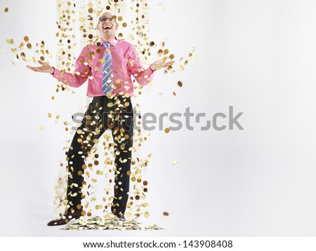 Full length of a happy male executive under shower of gold coins against white background - stock photo