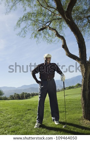 Full length of a happy senior African American man on golf course - stock photo
