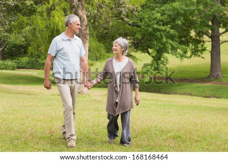 Full length of a happy senior couple holding hands and walking in the park - stock photo
