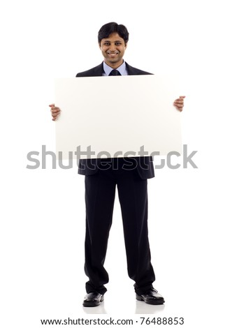 Full length of a happy young Indian businessman holding blank sign- copyspace isolated over white background - stock photo