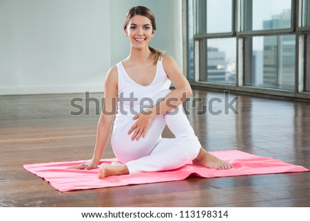 Full length of a happy young woman in Half Spinal Twist pose on mat - stock photo