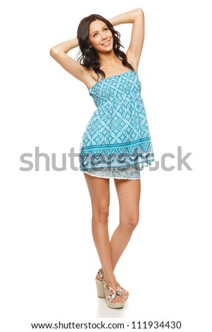 Full length of a happy young woman standing with hands behind head, against white background - stock photo