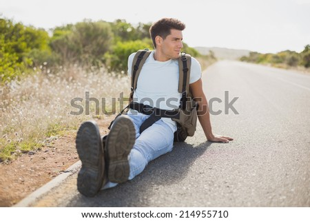 Full length of a hiking man sitting on countryside road