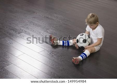 Full length of a little boy sitting on hardwood floor with soccer ball - stock photo