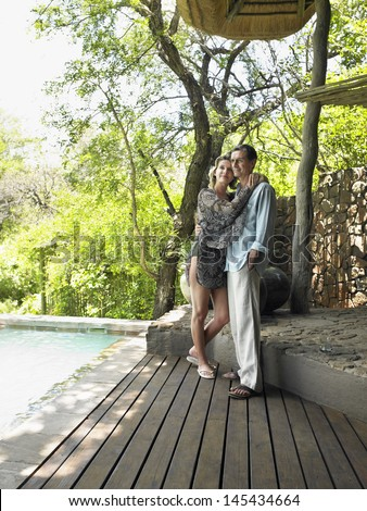 Full length of a loving couple embracing on resort terrace - stock photo