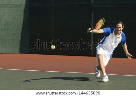 Full length of a male tennis player hitting backhand on the tennis court - stock photo