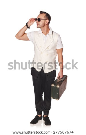 Full length of a man with suitcase standing over white background looking away in concentration
