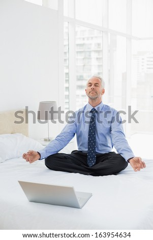 Full length of a mature businessman sitting in lotus pose with laptop on bed at home