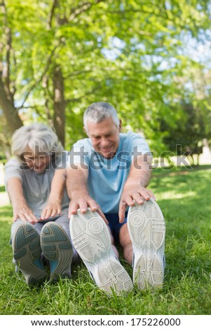 Full length of a mature couple stretching hands to legs at the park - stock photo