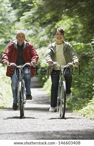 Full length of a mature man and middle aged woman biking on forest road - stock photo