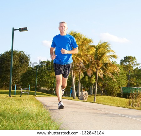 Full length of a mature man jogging. Horizontal shot. - stock photo