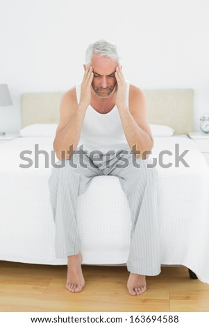 Full length of a mature man suffering from headache in bed at home