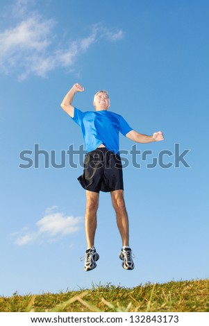Full length of a mature sporty man jumping in air with hand raised against sky. Vertical shot.