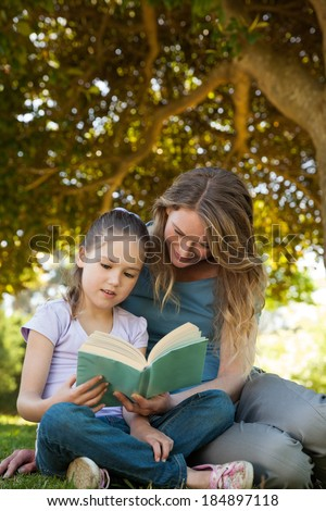 Full length of a mother and daughter reading a book at the park - stock photo