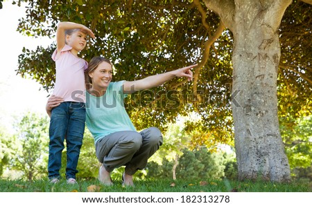 Full length of a mother pointing out at something besides daughter at the park - stock photo