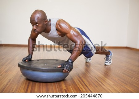 Full length of a muscular man doing push ups in gym - stock photo