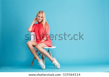 Full length of a pretty casual woman in red dress sitting and looking at camera isolated on the blue background