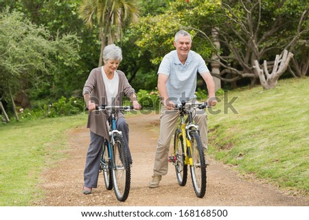 Full length of a senior couple on cycle ride in countryside - stock photo