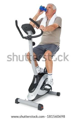 Full length of a senior man drinking water on stationary bike over white background - stock photo