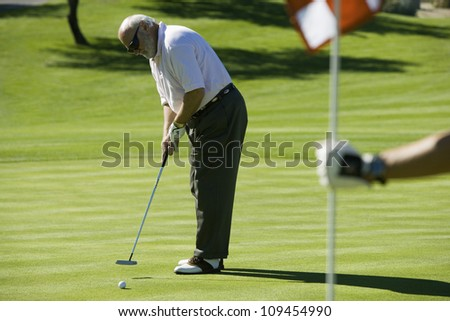 Full length of a senior man playing golf at golf course - stock photo