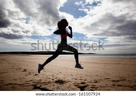 Full length of a silhouette healthy young woman jogging on shore at beach - stock photo