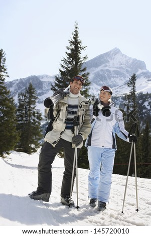 Full length of a skiing couple with skis standing on ski slope - stock photo