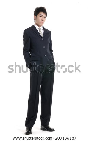 Full length of a smiling young businessman walking in studio