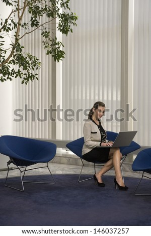 Full length of a smiling young businesswoman using laptop in office lobby