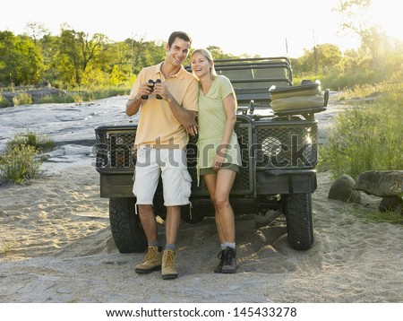 Full length of a smiling young couple standing by jeep with binoculars  - stock photo