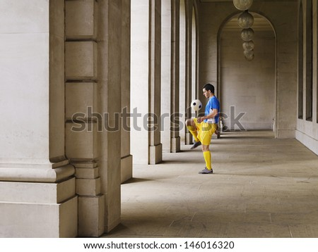 Full length of a soccer player bouncing ball off knee in portico - stock photo