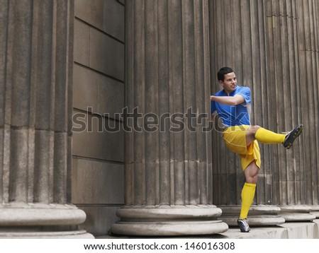 Full length of a soccer player kicking ball between columns - stock photo