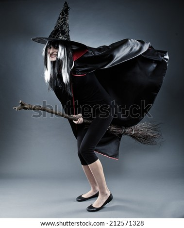 Full length of a sorcerer with hat and cape and broom