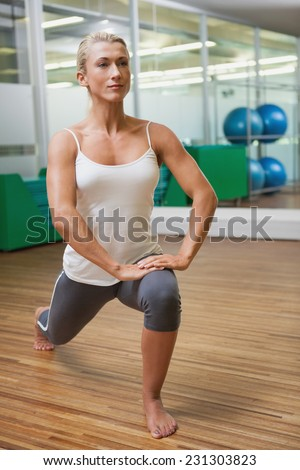 Full length of a sporty young woman doing power fitness exercise at yoga class