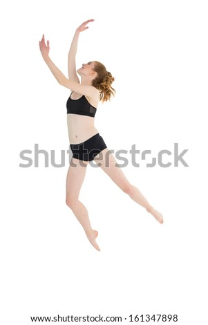 Full length of a sporty young woman jumping over white background