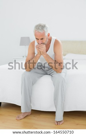 Full length of a thoughtful mature man sitting in bed at home
