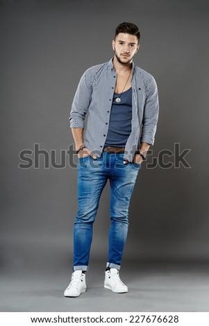 Full length of a trendy fashionable man, studio shot - stock photo
