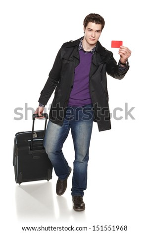 Full length of a walking young smiling male wearing autumn jacket and pulling the suitcase showing empty credit card - stock photo